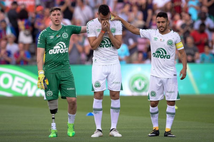 Chapecoense's defender Neto (C) cries between Chapecoense's goalkeeper Jakson Follmann (L) and Chapecoense's defender Alan Ruschel before the 52nd Joan Gamper Trophy friendly football match between Barcelona FC and Chapecoense at the Camp Nou stadium in Barcelona on August 7, 2017. / AFP PHOTO / Josep LAGO