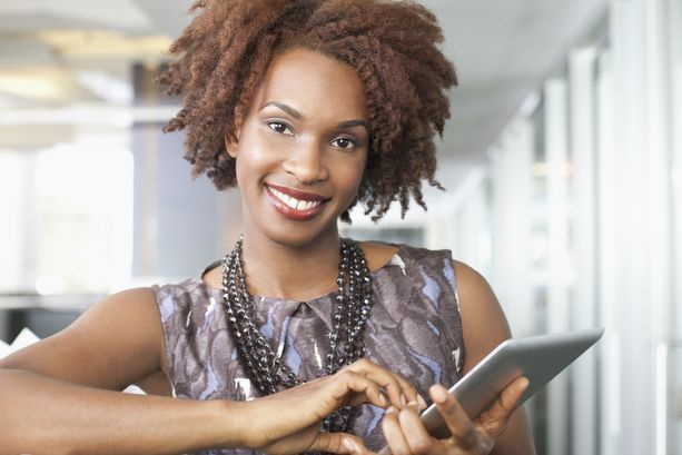 Young smiling woman holding digital tablet, portrait --- Image by © Josef Lindau/Corbis